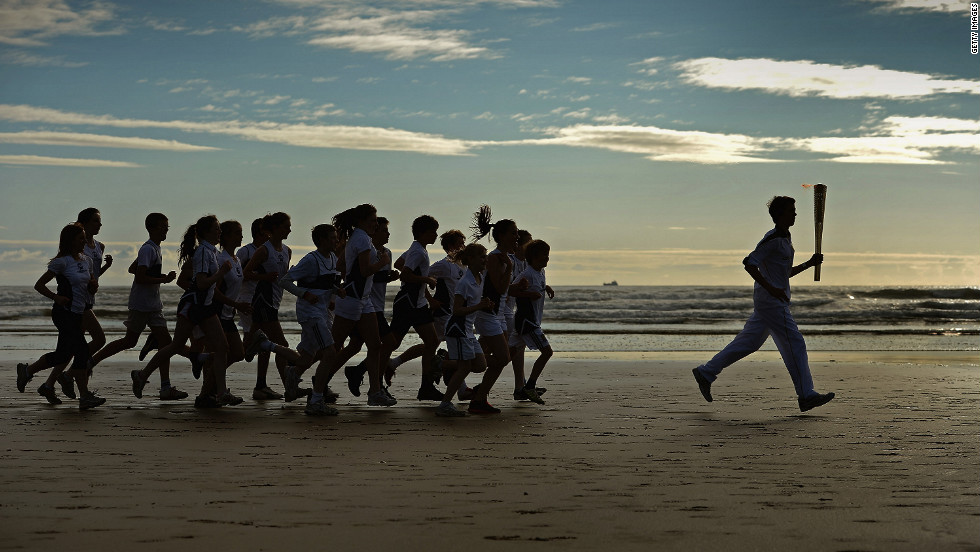 Joseph Forrester, 12, and children from Madras College run along West Sands in St. Andrews, Scotland, on June 13.