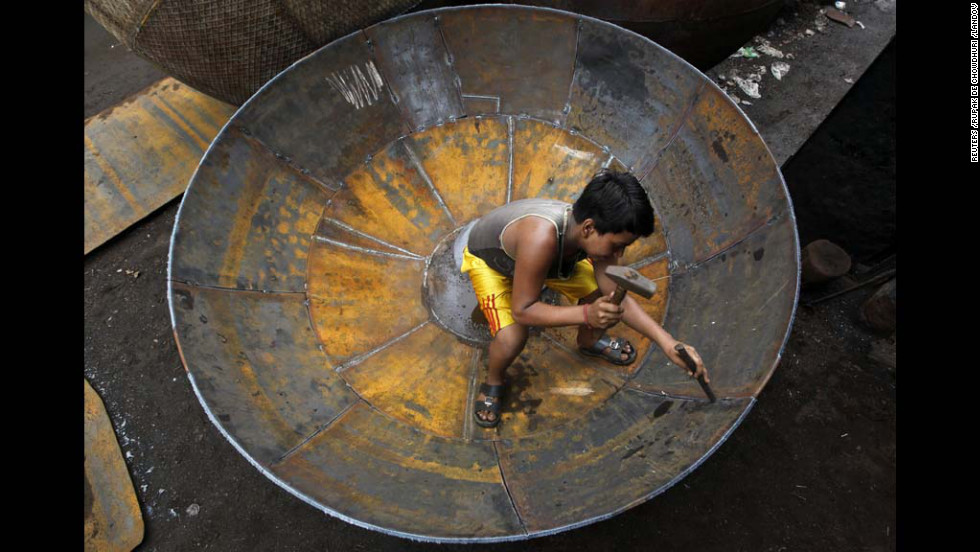 A boy checks the joints of a giant utensil at an iron utensils manufacturing unit Thursday in Kolkata, India.