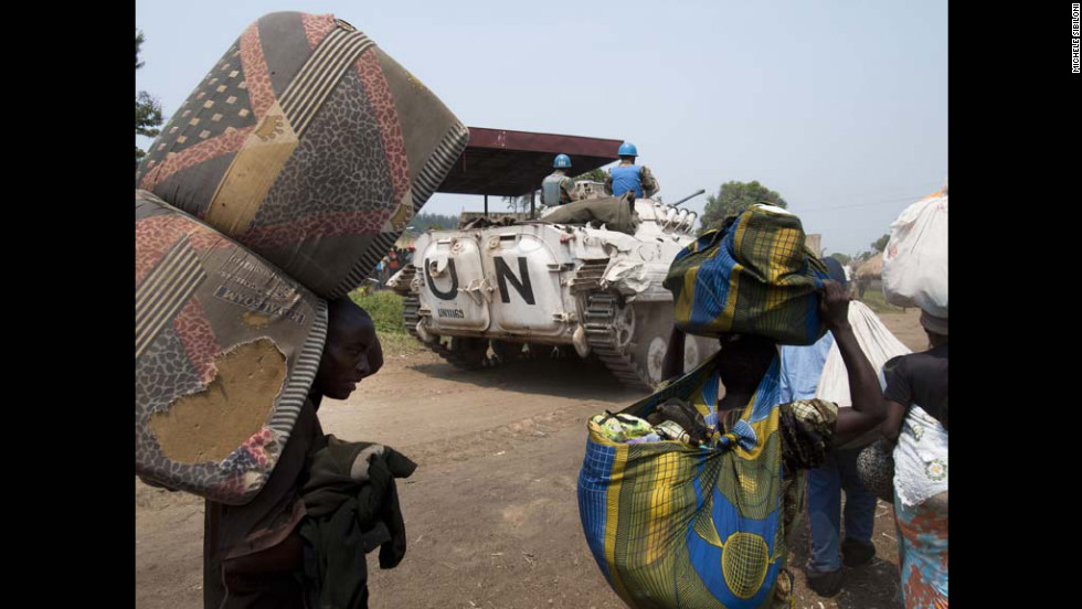 A UN peacekeepers travel along the road with refugees headed for the Kiwanja refugee camp.