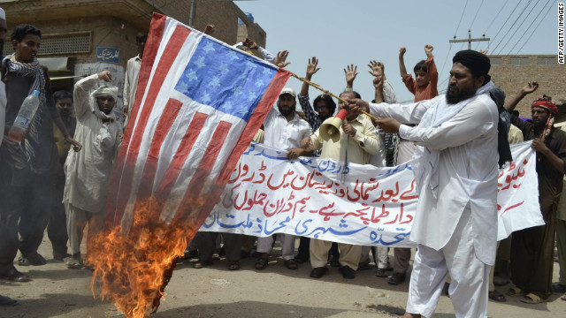 A man burns the U.S. flag in protest of a drone strike in Multan, Pakistan, on July 7.
