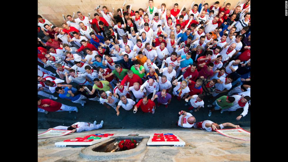 Revelers sing el cantico a San Fermin under the San Fermin statue on la cuesta de Santo Domingo on Friday.