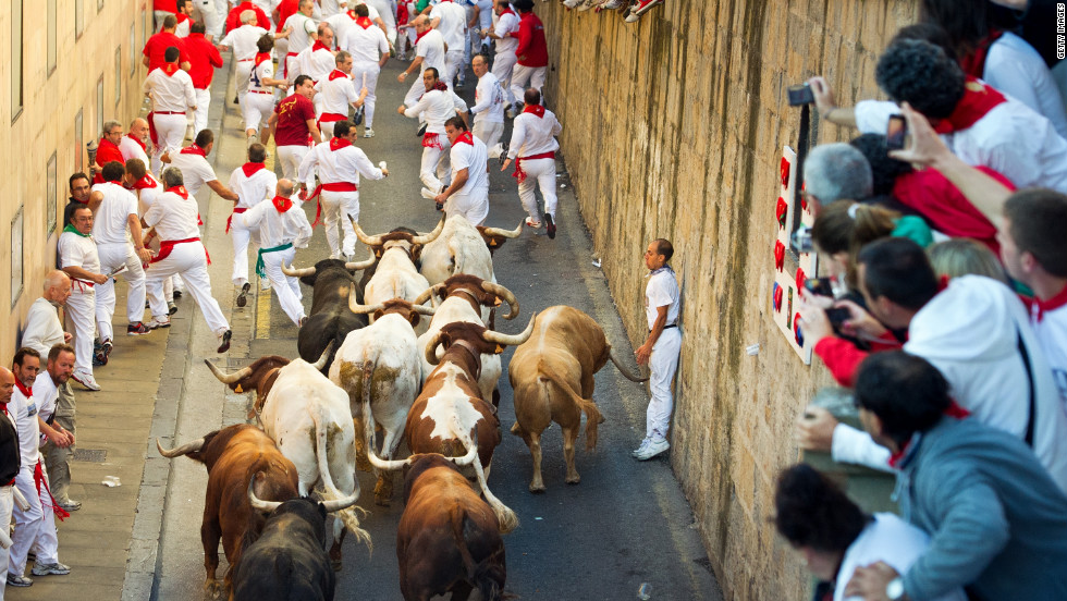 People take pictures as participants run by during the Running of the Bulls in Pamplona, Spain, on Friday, July 13.