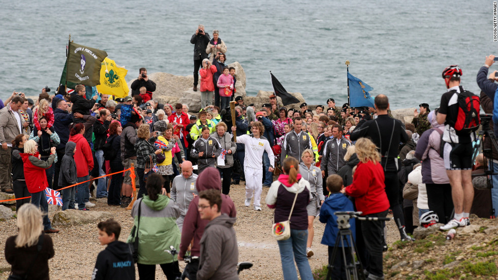 Thomas Mules carries the Olympic flame on Pulpit Rock, Portland Bill, on Friday, July 13.