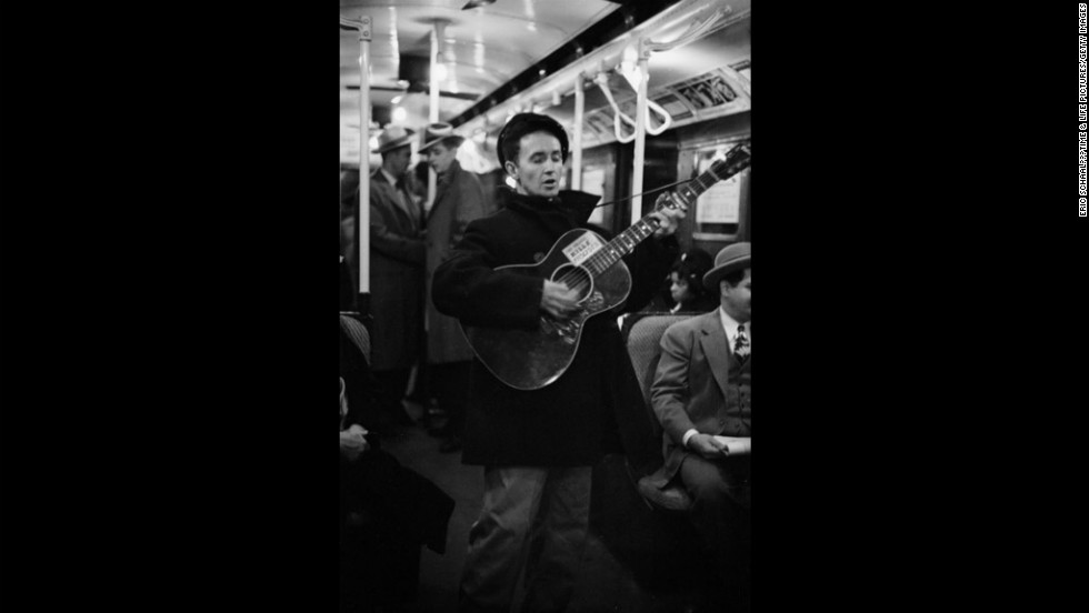 "Woody Guthrie entertains New York commuters in 1943, strumming a guitar bearing his now-famous slogan, ""This Machine Kills Fascists."""