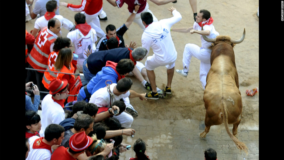 Spectators watch as a participant is hit by a bull Saturday.