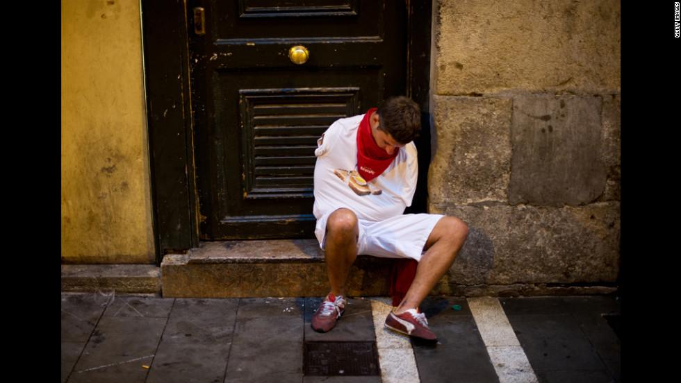 A man sleeps at the entrance of the bullring before the next run starts.