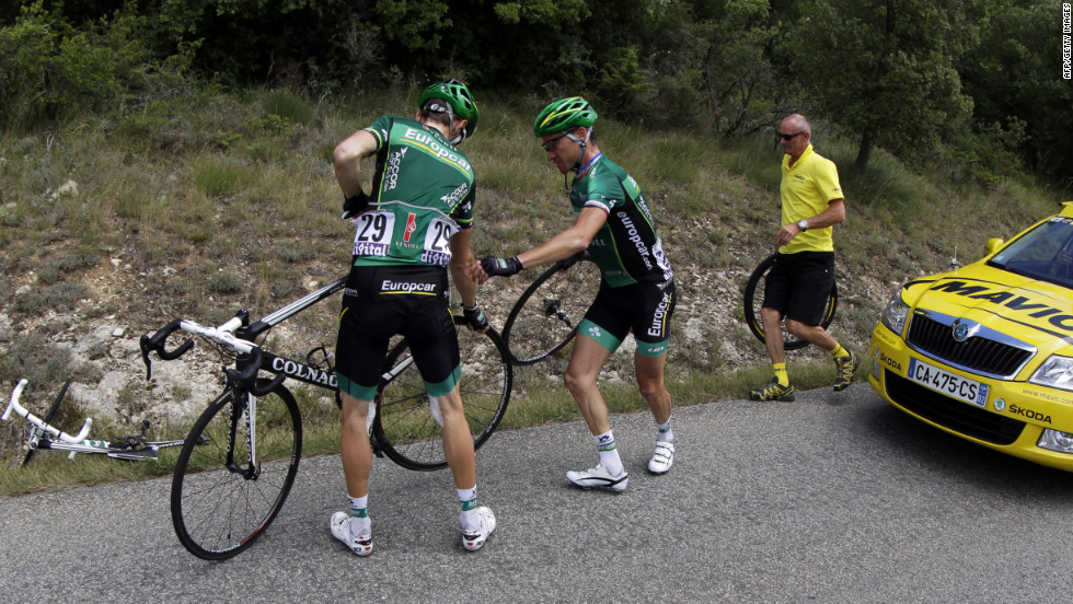 France's Thomas Voeckler, center, helps teammate Pierre Rolland of France, left, change a wheel during the race Sunday. Around 30 punctured tires were reported near the top of the last major climb, apparently caused by tacks thrown on the course by spectators.
