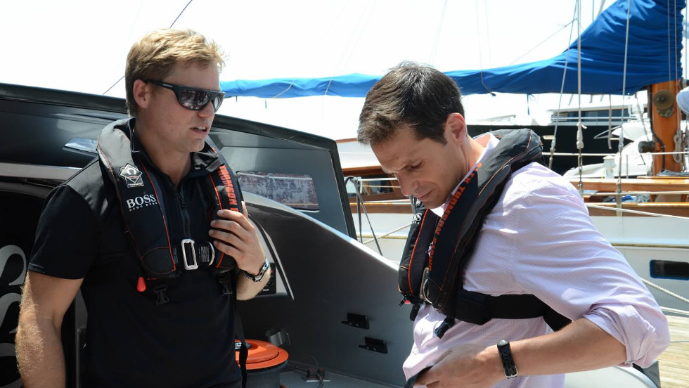 """Early Start"" co-anchor John Berman getting a tip on life jacket safety from Alex Thomson before taking a test ride."