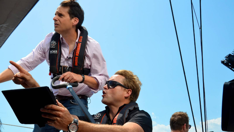 Alex Thomson shows John Berman how to use an iPad to help navigate the ride on the Hudson River in New York City.