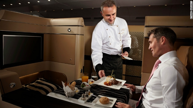 An Etihad Airways chef serves up an in-flight meal to a passenger in the first-class cabin.