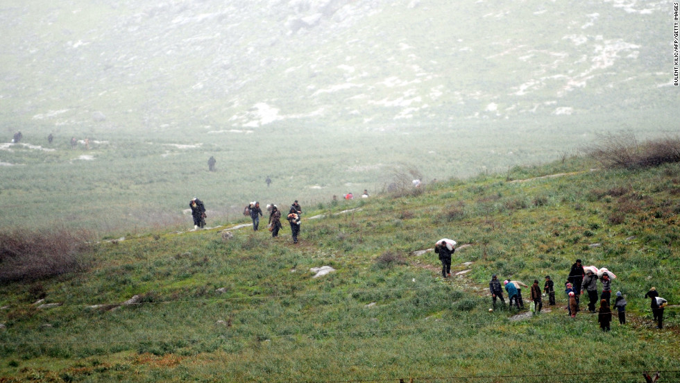 Syrian refugees walk across a field before crossing into Turkey on March 14, 2012.