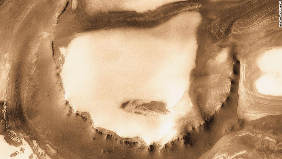 Although it is 45 kilometers (28 miles) wide, countless layers of ice and dust have all but buried the Udzha Crater on Mars. The crater lies near the edge of the northern polar cap. This image was taken by NASA's Mars Odyssey Orbiter in 2010.