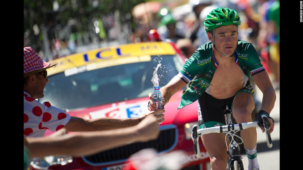 Stage winner Thomas Voeckler of France grabs a bottle of water from a fan as he climbs the final pass before the finish Wednesday, July 18, during the 197-kilometer (122-mile) race through the Pyrenees from Pau to Bagnères-de-Luchon.