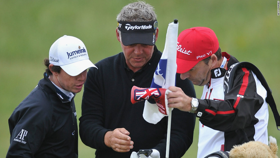 For the first time since 2006, the British Open will allow fans to bring phones onto the golf course when it gets underway on Thursday. Darren Clarke (center), who went on to lift the Claret Jug in 2011, and Rory McIlroy can be seen here checking out a phone during a practice round ahead of last year's event.