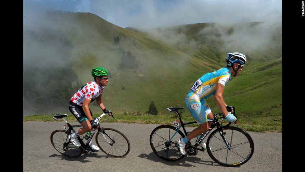 Thomas Voeckler of France and Fredrik Kessiakoff of Sweden ride in a breakaway group together through the Pyrenees mountains.