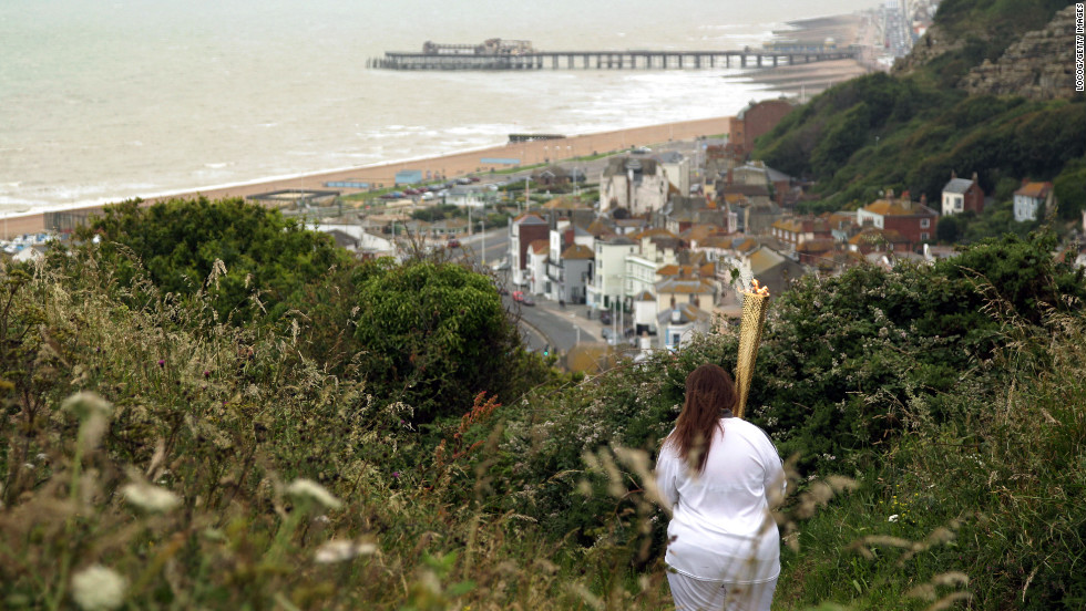 Torchbearer Daisy Shepherd of East Sussex carries the Olympic flame through Hastings on the southern coast of England on Wednesday, July 18.