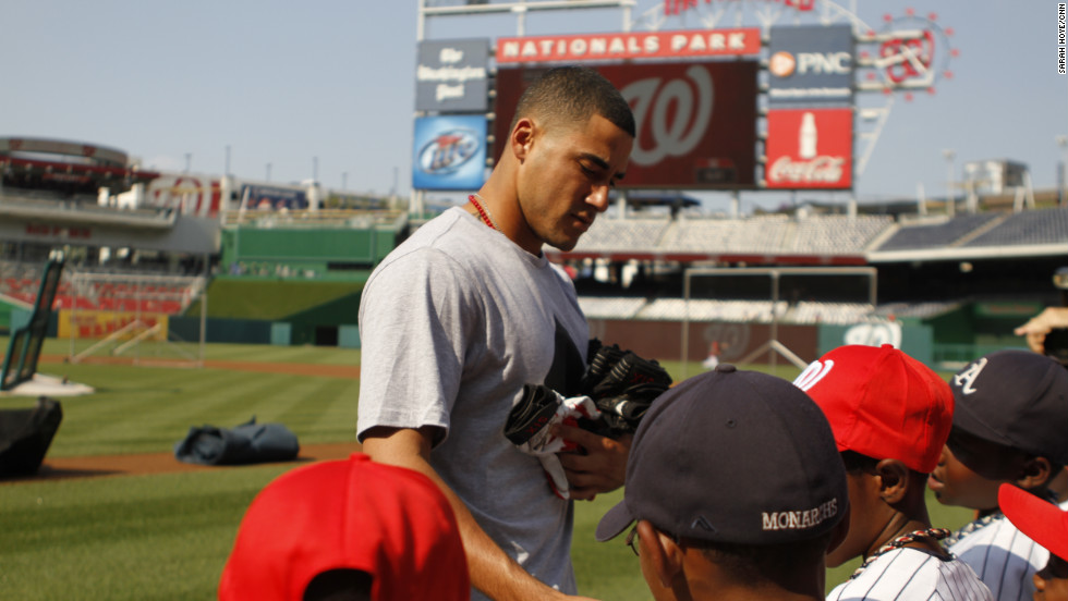 Here, Washington Nationals shortstop Ian Desmond passes out batting gloves to the team at Nationals Park.  It is one of several Major League Baseball parks the inner city Little League team is visiting this summer as a tribute to Jackie Robinson and the Negro Leagues.