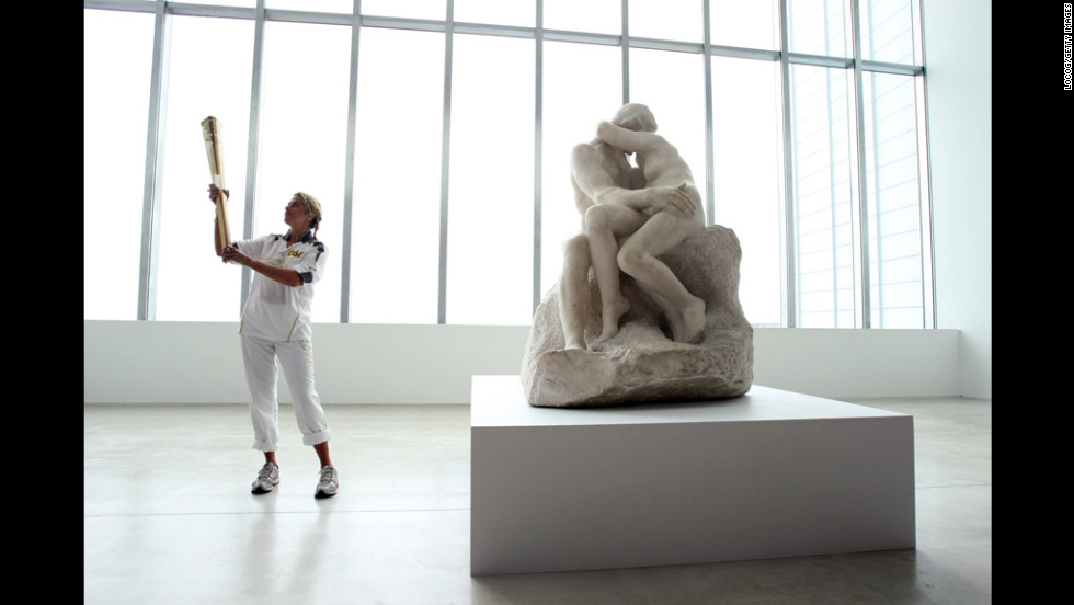 "British artist Tracey Emin holds the Olympic flame inside the Turner Contemporary Gallery in Margate alongside ""The Kiss"" sculpture by Rodin on Thursday, July 19."
