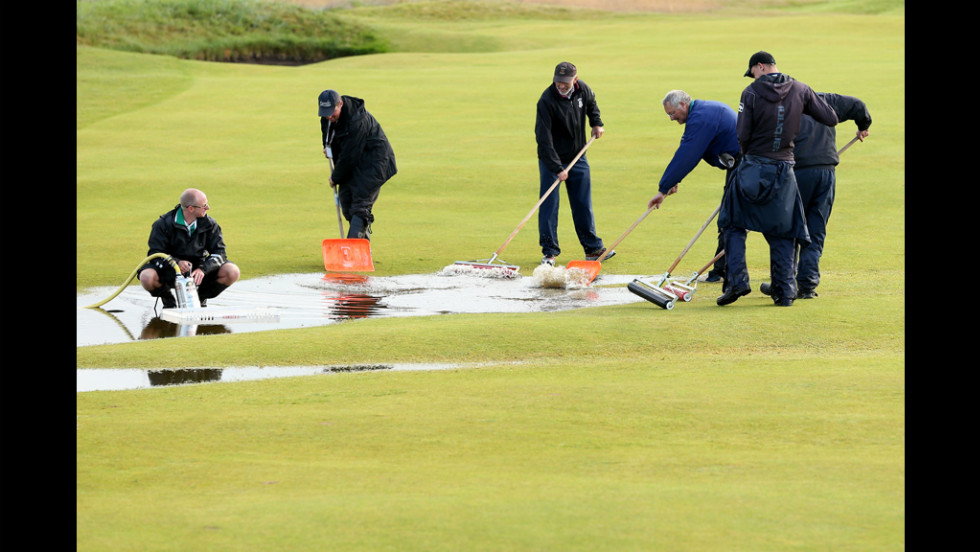 Members of the grounds crew clear water on the course Friday during the second round.