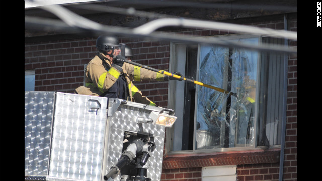 Police break the window of the apartment of Colorado shooting suspect, James Holmes, on Friday.