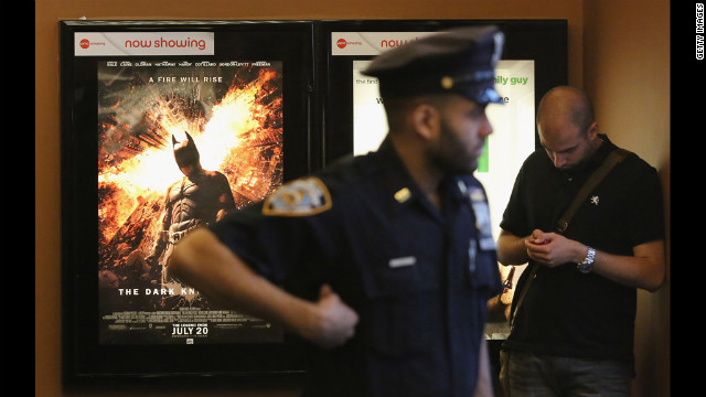 An NYPD officer keeps watch inside an AMC move theater where the film 'The Dark Knight Rises' is playing in Times Square on Friday. NYPD  is maintaining security around city movie theaters following the deadly rampage in Aurora, Colorado.