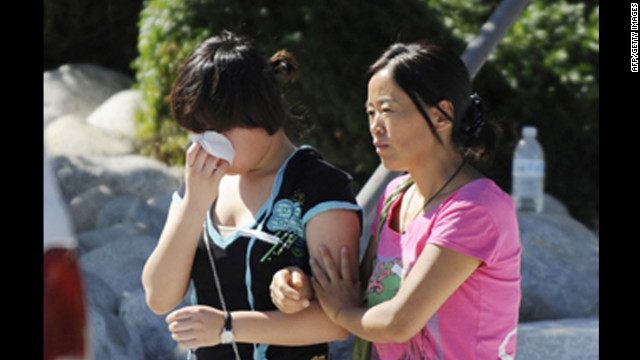 Lin Gan wipes away her tears as her mother, Juan Gan, guides her to their car after meeting with counselors at the Gateway High School in Aurora on Friday.