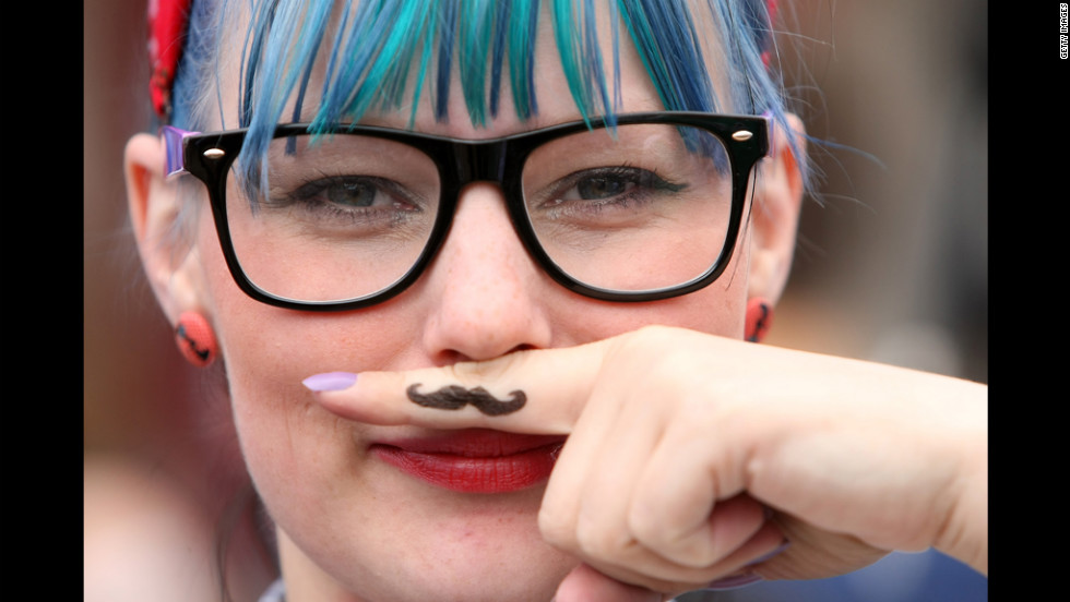 "A woman attending the Hipster Olympics 2012 holds her finger to her face, displaying a drawn-on ""ironic mustache"" Saturday, July 21."