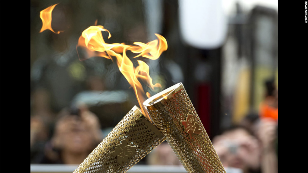 "Torchbearers ""kiss"" their torches to pass the Olympic flame during the London 2012 torch relay through the Borough of Tower Hamlets in London on Saturday, July 21."