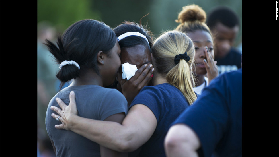 Mourners hug as they grieve the loss of the victims.