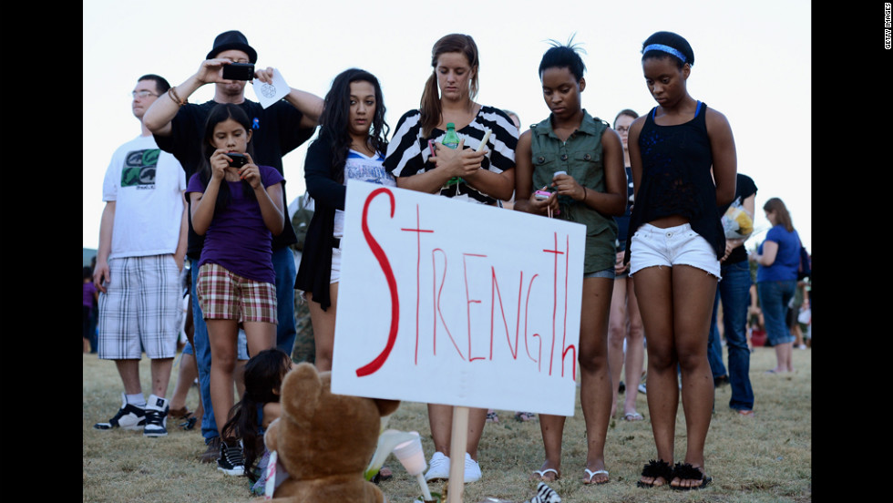 "A group of teenagers stand behind a sign that reads ""Strength."""