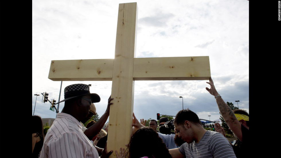 People pray at a cross erected at the makeshift memorial across the street from the Century 16 theater on Saturday.