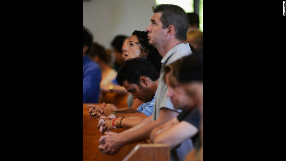 Parishioners pray during morning Mass, remembering victims of the theater shooting, at the Queen of Peace Catholic Church on Sunday.