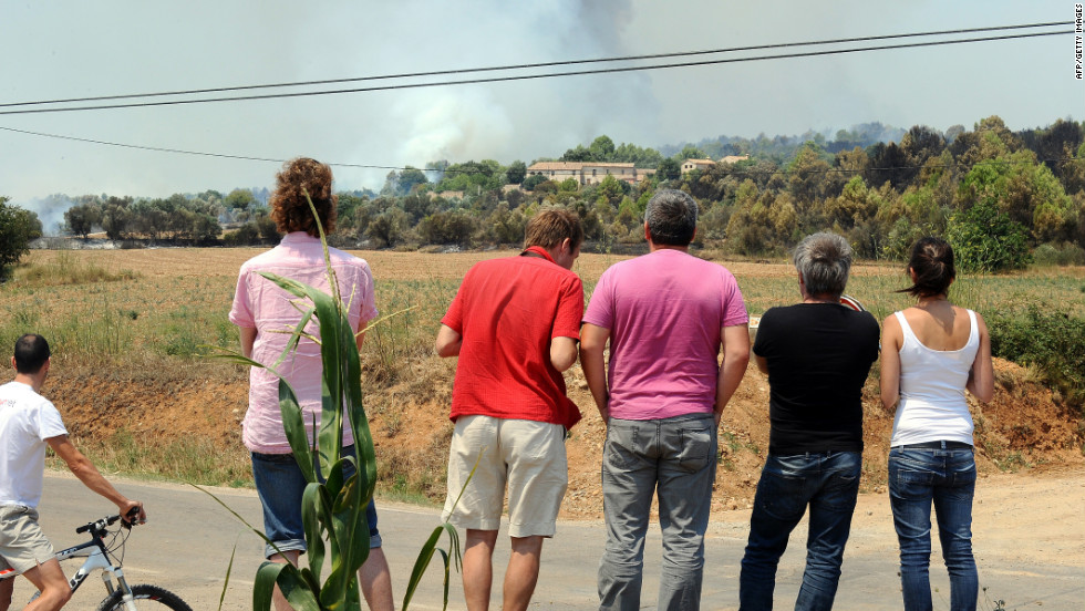 Residents watch as a plume of smoke rises near Figueras on Monday.