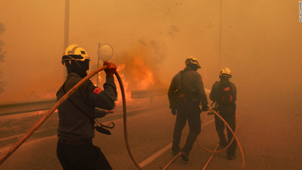 Firefighters are engulfed in smoke as they battle the wildfire in Altemporada on Sunday.