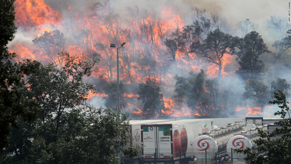 A wildfire approaches a group of trucks parked in a lot in La Jonquera on Saturday, July 21.
