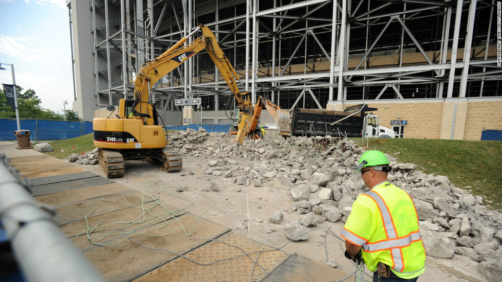 Workers on Tuesday, July 24, remove the concrete landing area and wall where the Joe Paterno statue once stood in State College, Pennsylvania.