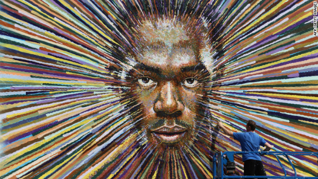 Street artist James Cochran puts the finishing touches to a piece of work depicting the face of Jamaican sprinter Usain Bolt on July 20, 2012 in London, England.