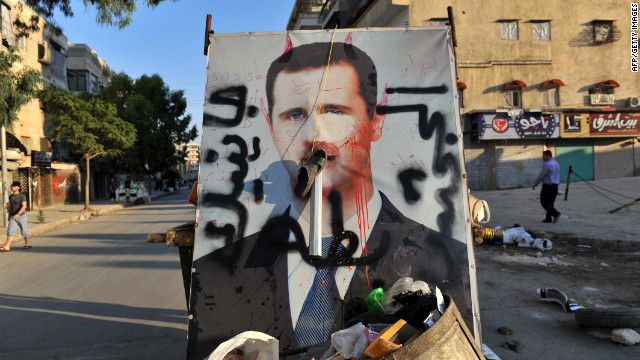A vandalized poster of Syrian President Bashar al-Assad lies in a trash container in the northern city of Aleppo on Tuesday.