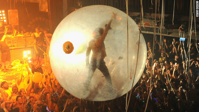 The Flaming Lips' Wayne Coyne surfs a concert crowd in his space bubble.