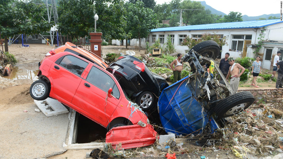 As the floodwater cleared, the damage became clearer. These cars are wedged in a hole in Beijing, July 23, 2012.