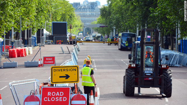 Workers put final touches on the Mall near Buckingham Palace. The Mall closes to traffic during the Games, irritating many Britons.
