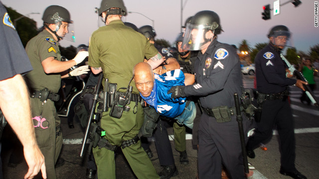 ANAHEIM, CA - JULY 24: A protester is taken into custody during a demonstration to show outrage for the fatal shooting of Manuel Angel Diaz, 25, at Anaheim City Hall on July 24, 2012 in Anaheim, California. Diaz was fatally shot on July 21 by an Anaheim police officer and has sparked days of protests by the angered community. (Photo by Jonathan Gibby/Getty Images)