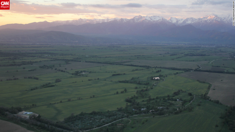 """Asel Shilikbayeva of Manchester, England, was in flight to Almaty when she took this photo of the sun setting behind the Tian Shan Mountains. """"The view of the mountains lit by the fiery red sky and the green landscape was breathtaking,"""" she says."""