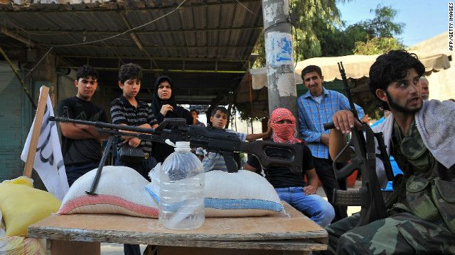 Syrian people stand next to a checkpoint manned by rebels in the northern city of Aleppo on July 24, 2012.