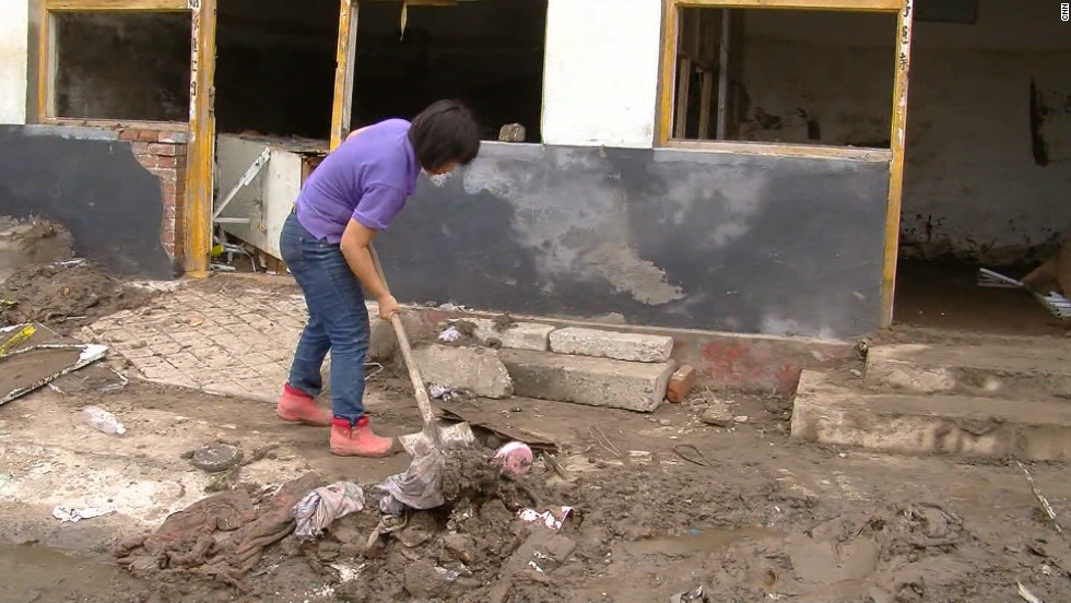 A woman cleans mud from her home in the Fangshan district of Beijing, China, July 25, 2012