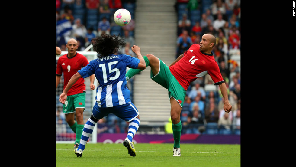 Morocco's Houssine Kharja, right, controls the ball against Honduras' Roger Espinoza during a first-round Group D match Thursday in Glasgow, Scotland.