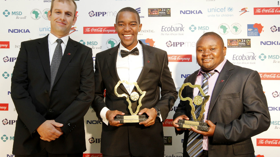 Certainly happy about the win, joint winners Waihiga Mwaura (center) and Jephitha Mwai Mwangi (right) smile after they are awarded the Sport Award for their work on Maasai cricket warriors on Citizen TV in Kenya.