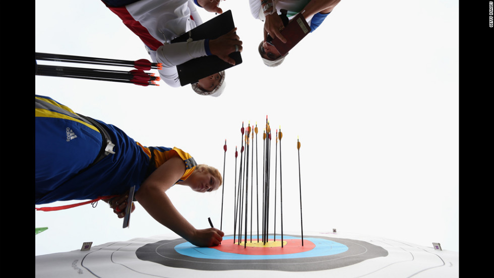 Kaori Kawanaka of Japan, Pia Lionetti of Italy and Tetyana Dorokhova of Ukraine retrieve their arrows Friday during the archery ranking round on opening day of the Olympics in London.