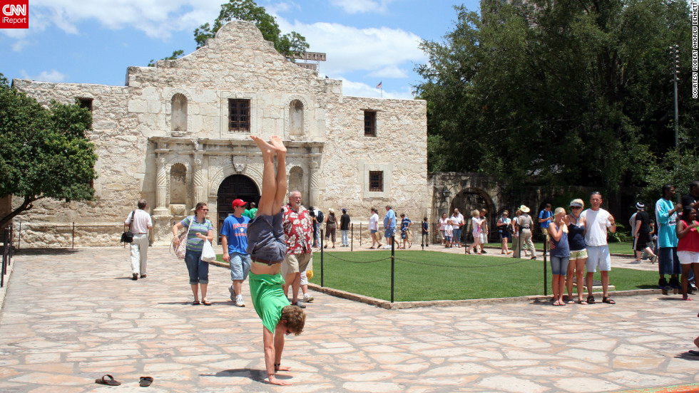 iReporter Andrew Bennett started doing handstands in front of landmarks while he was studying abroad in 2007. His handstand in front of The Alamo in 2008 draws some interest from other visitors