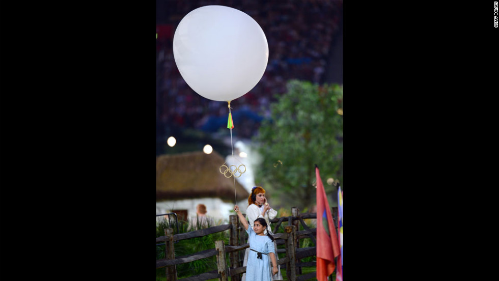 A young performer holds a balloon bearing the Olympic rings.